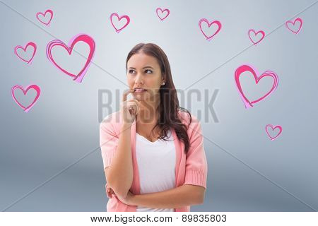 Pretty brunette thinking with finger to mouth against grey vignette
