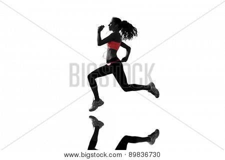 Full length of healthy woman jogging against mirror