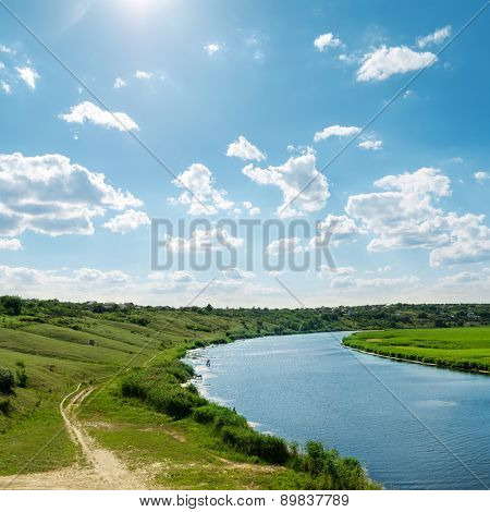 sun in blue sky with clouds over river