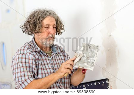 Builder Or Homeowner Repairing A Wall