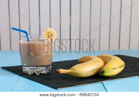 Healthy homemade chocolate banana smoothie in glass and fresh bananas on light wooden background.
