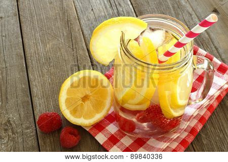 Detox water with lemon and raspberries in mason jar glass