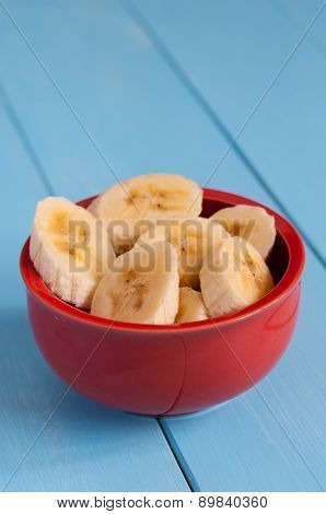 Sliced banana in pot over a blue table.