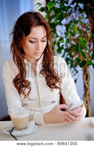 Beautiful Girl Sits In Cafe And Reads Sms On Phone