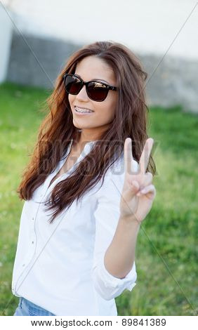 Brunette cool girl with sunglasses in the park gesturing the victory signal