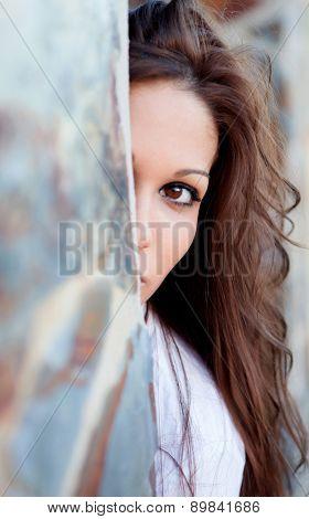 Pretty brunette girl hidden behind a wall