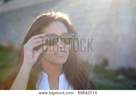 Brunette cool girl with sunglasses in the park
