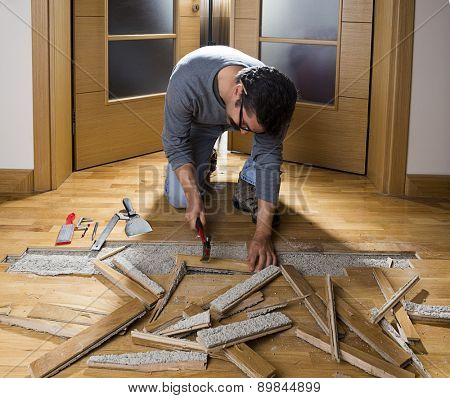 Manual worker disassembling wooden floor ruined from moisture and water leak