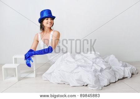 Happy Bride Sitting On The Floor In A Hat And Blue Gloves,