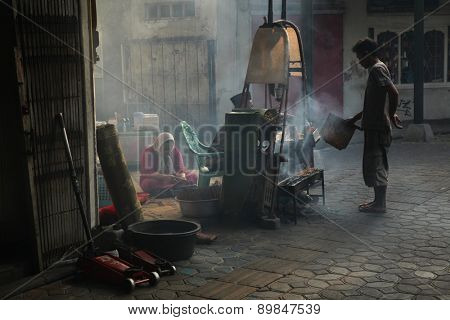 SURAKARTA, INDONESIA - AUGUST 17, 2011: Vendors prepare and sell street food in Surakarta, Central Java, Indonesia.