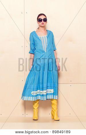 Full-length portrait woman in romantic dress on wodden background