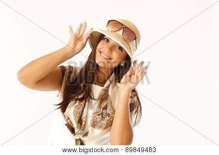 Summer portrait of attractive young woman regulating hat, smiling happy.