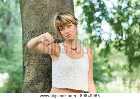 Blonde young woman outdoors doing thumb down sign