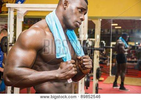 Hunky muscular black bodybuilder resting after workout