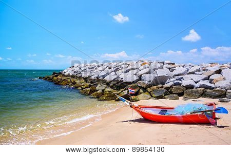 Stone Breakwater And Rowboat At The Beach