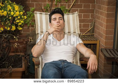 Handsome dark haired young man smoking a cigarette in a balcony, in summer