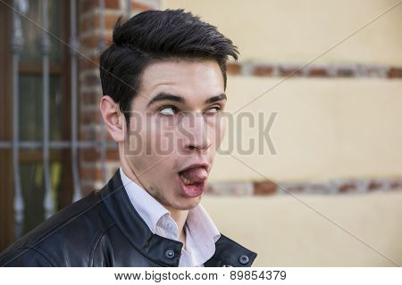 Young man outdoor doing silly face and stupid expression