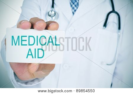 a young caucasian doctor shows a signboard with the text medical aid