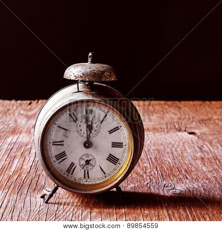 a rusty old alarm clock on a rustic wooden table, with a black background