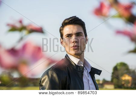 Good looking male model at couuntryside, among flowers