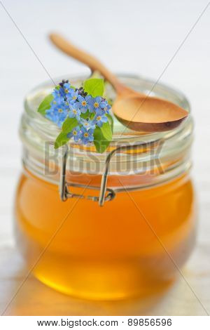 glass jar full of honey and spoon