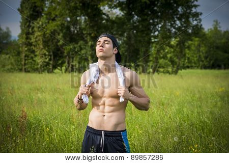 Handsome shirtless fit young man at countryside, resting after jogging