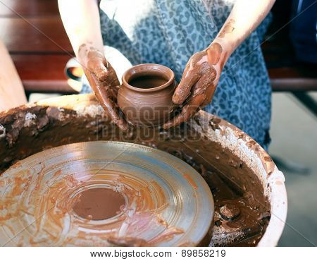 Ceramic jug in dirty potter's hands