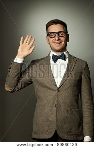 Nerd in eyeglasses and bow tie says Hello against grey background