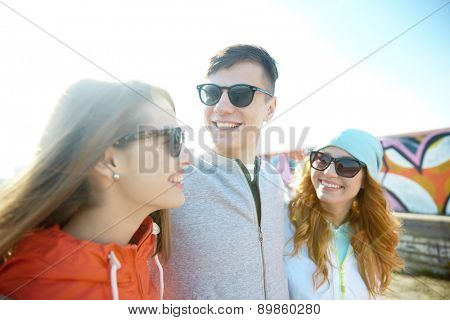 tourism, travel, people, leisure and teenage concept - group of happy friends in sunglasses hugging and talking on city street