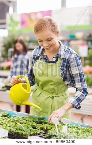 people, gardening and profession concept - happy woman or gardener with watering can and seedling in greenhouse