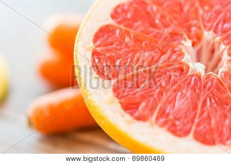 healthy eating, food, fruits and diet concept - close up of fresh juicy grapefruit slice on table