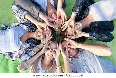 summer holidays, friendship, leisure and teenage concept - group of students or teenagers lying in circle and having fun at campus or park