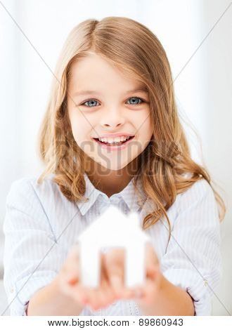 home and family concept - little girl holding white paper house