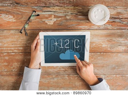 people, weather forecast and technology concept - close up of hands with metcast on tablet pc screen