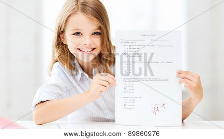 education and school concept - little school girl with test and A grade at school