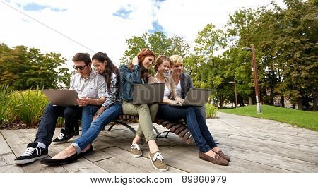 summer, communication, technology , education and teenage concept - group of students or teenagers with laptop computers at park or campus