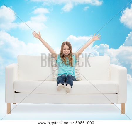 home, leisure, people and happiness concept - smiling little girl sitting on sofa with raised hands over blue sky and white clouds background