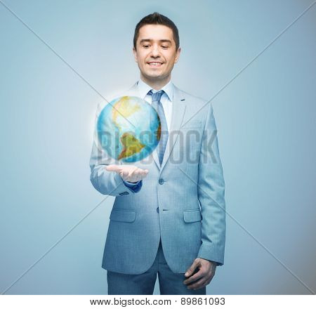 business, people, communication, geography and education concept - happy businessman in suit showing or holding globe hologram on palm over blue background