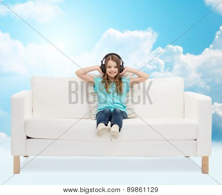 leisure, technology, music and childhood concept - smiling little girl in headphones listening to music sitting on sofa over blue sky and white clouds background