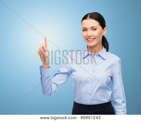 business, technology and people concept - businesswoman pointing finger to or touching something imaginary over blue background