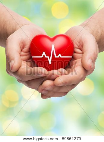 family health, charity and medicine concept - close up of hands holding red heart with cardiogram over green lights background