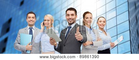 business, people and gesture concept - group of smiling businessmen showing thumbs up over office building background