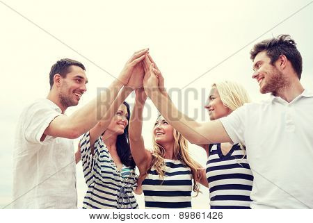 friendship, happiness, unity and people concept - smiling friends in striped clothes making high five gesture outdoors