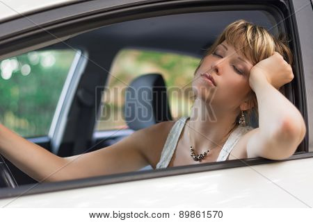 Attractive blonde young woman sleeping in a car