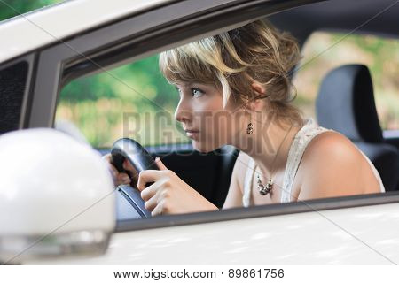 Young Woman Learning to Drive Car and Leaning Forward
