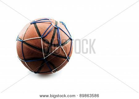 Old basketball ball in a net isolated on white background.