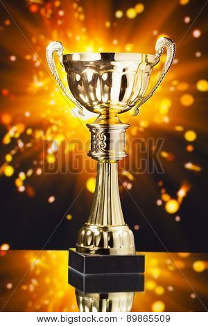 gold cup trophy against shiny sparks background