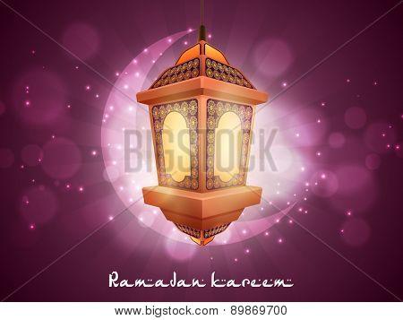 Hanging illuminated arabic lamp with crescent moon on shiny purple background for holy month of muslim community, Ramadan Kareem celebration.