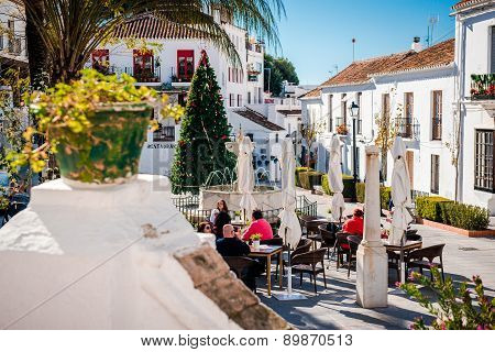 Tourists Sitting In A Sidewalk Cafe On Central Street Of Mijas