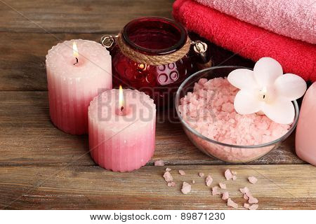 Spa still life with candlelight and sea salt on wooden background